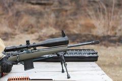 En man skjuter ett gevär Plundra skytte med optisk sikt utomhus vid mannen Royaltyfri Bild