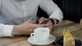 En man skriver ett meddelande genom att använda hans mobiltelefon på aftonen Tid i kafé Närbild av hans händer stock video