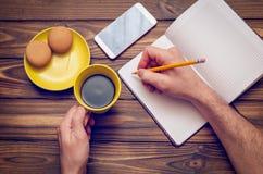 En man skriver något i en anteckningsbok med en gul kopp kaffe och en telefon på en trätabell arkivfoto