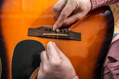 En man som ändrar den gamla rev sönder gitarren, stränger på den akustiska gitarren Royaltyfri Fotografi