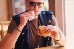 En man som äter en strikt vegetarianhamburgare royaltyfria foton