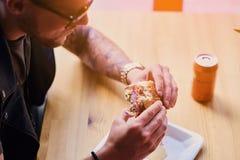 En man som äter en strikt vegetarianhamburgare royaltyfria bilder