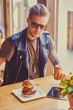 En man som äter en strikt vegetarianhamburgare arkivfoto