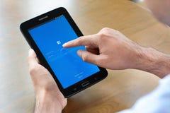 En man som använder den Fackbook applikationen på minnestavlan för Samsung galax Tab3 Arkivbild