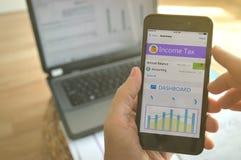 En man som använder en mobil app för att beräkna hans inkomstskatt Arkivbilder