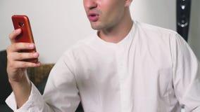 En man som använder hans smartphone se till och med erotiskt innehåll han flörtar samtal på videoen arkivfoton