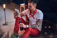 En man som använder minnestavlaPC i ett rum med vindinre fotografering för bildbyråer