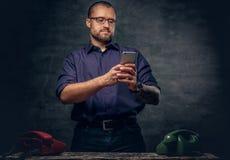 En man som använder en smart telefon i ett rum med parallella mobiltelefoner Fotografering för Bildbyråer