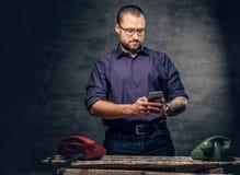 En man som använder en smart telefon i ett rum med parallella mobiltelefoner Arkivfoton