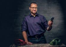 En man som använder en smart telefon i ett rum med parallella mobiltelefoner Royaltyfri Foto