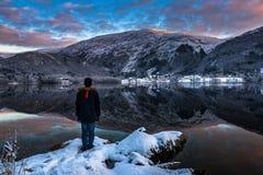 En man som bara står vid sjön i vinter på skymning royaltyfria bilder