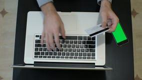 En man som betalar för online-shopping genom att använda bärbara datorn och kreditkorten Denna bild illustreras online-betalningb arkivfilmer