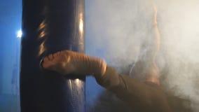 En man som boxas ett päron i idrottshallen lager videofilmer