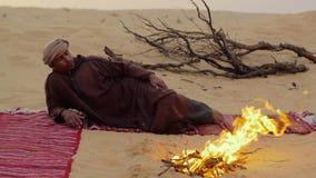 En man som campar i den sahara öknen lager videofilmer