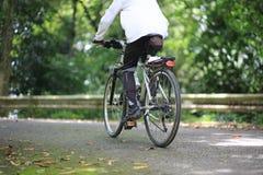 En man som cyklar i parkera Arkivbild
