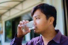 En man som dricker nytt kallt vatten royaltyfri bild