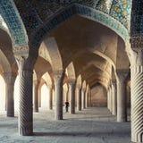 En man som går inom Shabestan av den Vakil moskén i Shiraz Arkivfoto