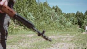 En man som går på en landsväg med ett prickskyttgevär i hans händer Härlig filmisk ram i ultrarapid arkivfilmer