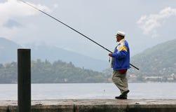 En man som går på en skeppsdocka på sjön med en metspö Royaltyfri Bild