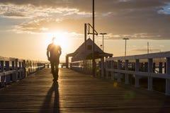 En man som går på solnedgången på pir Arkivfoto