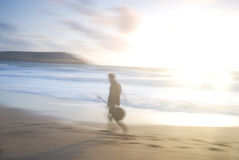 En man som går på strand med gitarren. Arkivfoto