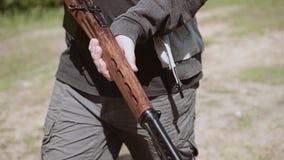 En man som går på vägen med ett prickskyttgevär Autentiska gamla vapen Härlig ultrarapidram lager videofilmer