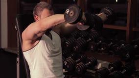 En man som gör övningar med hantlar i idrottshallen stock video