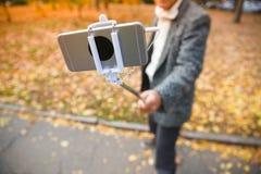 En man som gör selfie på en mobiltelefon med en monopod royaltyfri bild