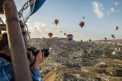 En man som i flykten som fotograferar från en korg av en ballong flyger luftballonger Fantastiskt område och ballonger arkivfoto