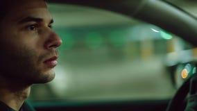 En man som kör bilen på undergroungparkering close upp bakgrundsbokehmusik bemärker tematiskt lager videofilmer