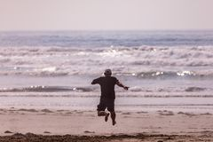 En man som kör in mot havet på en strand och gör ett stort hopp royaltyfri foto