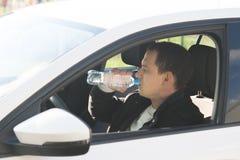En man som kör en vit bil som dricker kallt vatten från en flaska royaltyfria foton