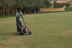 En man som klipper gräset på jordningen med maskinen Arkivbild