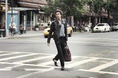 En man som korsar gatan i New York Fotografering för Bildbyråer
