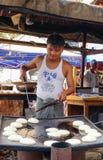 En man som lagar mat traditionella kakor på marknaden i Bagan, Myanmar Arkivfoto