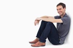 En man som ler, medan sitta mot en vägg Arkivbild