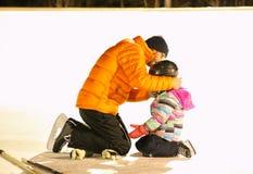 En man som lite hjälper den pålagda flickan en hockeyhjälm på en utomhus- isbana Royaltyfri Bild