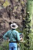 En man som målar vidskepelsebergen i den Apache föreningspunkten, Arizona Royaltyfri Bild