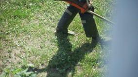 En man som mejar gräsgräsklipparen lager videofilmer