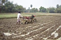 En man som odlar land vid en hand, risfältfält, vid handtraktoren royaltyfri fotografi
