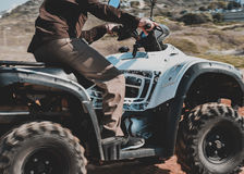 En man som rider ATV i sand i en hjälm royaltyfri foto