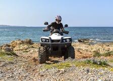 En man som rider ATV i sand i en hjälm fotografering för bildbyråer