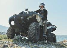En man som rider ATV i sand i en hjälm royaltyfri bild