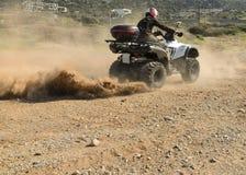 En man som rider ATV i sand i en hjälm arkivfoto