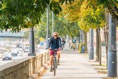 En man som rider en cykel på en cirkuleringsgränd i den Budapest Ungern Arkivbilder