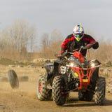 En man som rider det ATV-all-terräng medlet i sand i skyddskläder och en hjälm royaltyfria foton