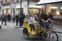 En man som rider en Rickshaw med lyckliga kvinnor i baksidan ner en gata i London Arkivbild