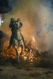 En man som rider hans hästbanhoppningthroug branden Royaltyfri Fotografi