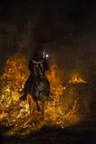 En man som rider hans hästbanhoppningthroug branden Royaltyfri Bild