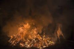 En man som rider hans hästbanhoppningthroug branden Arkivfoto